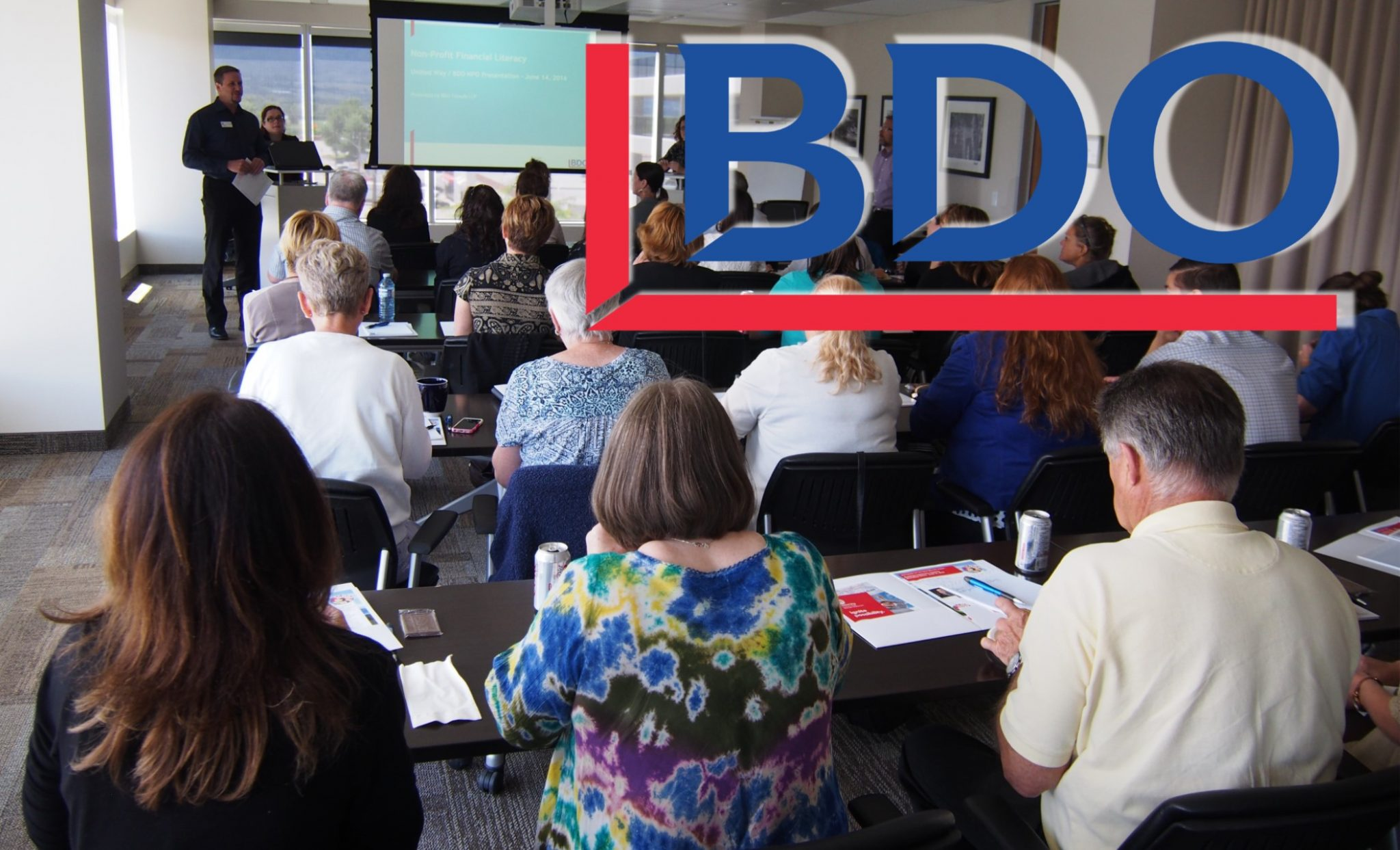 The BDO logo superimposed over an image of a group of people watching and taking notes on a presentation.