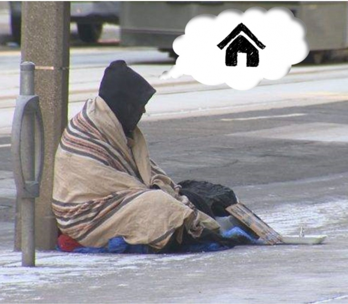 A person sits on the ground outside, wrapped in a blanket, with a thought bubble depicting an icon of a house.