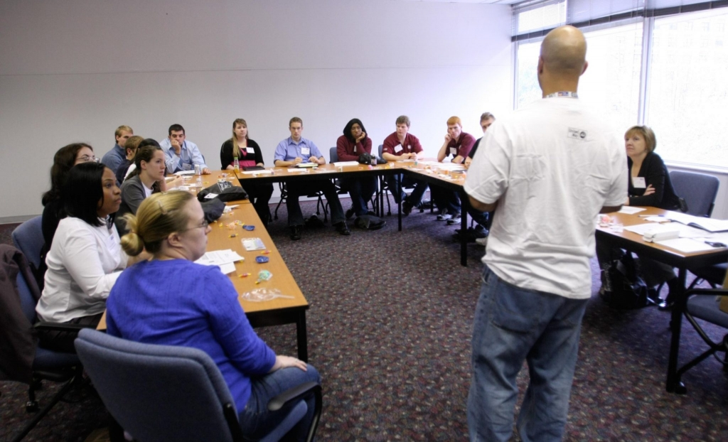 A person, standing, speaks to a large group of people seated at a U-shaped table.