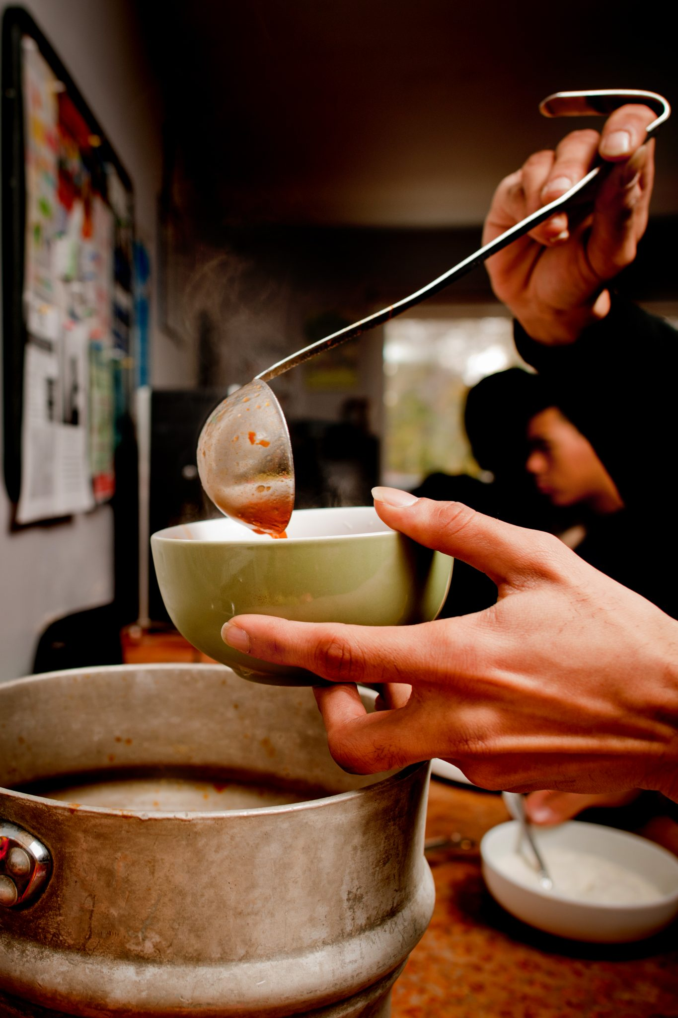 A ladle pours soup into a bowl held in a hand over a pot.