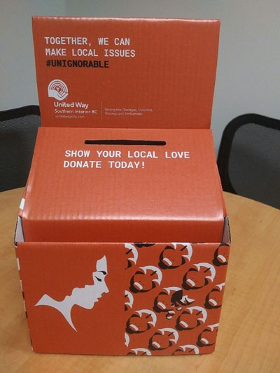 A cardboard donation box with a slot on the top. Text on it reads