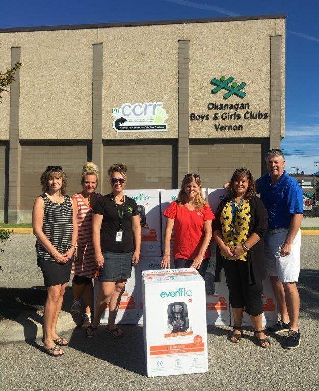 5 people standing in front of the Okanagan Boys and Girls Clubs Vernon with a carseat box.
