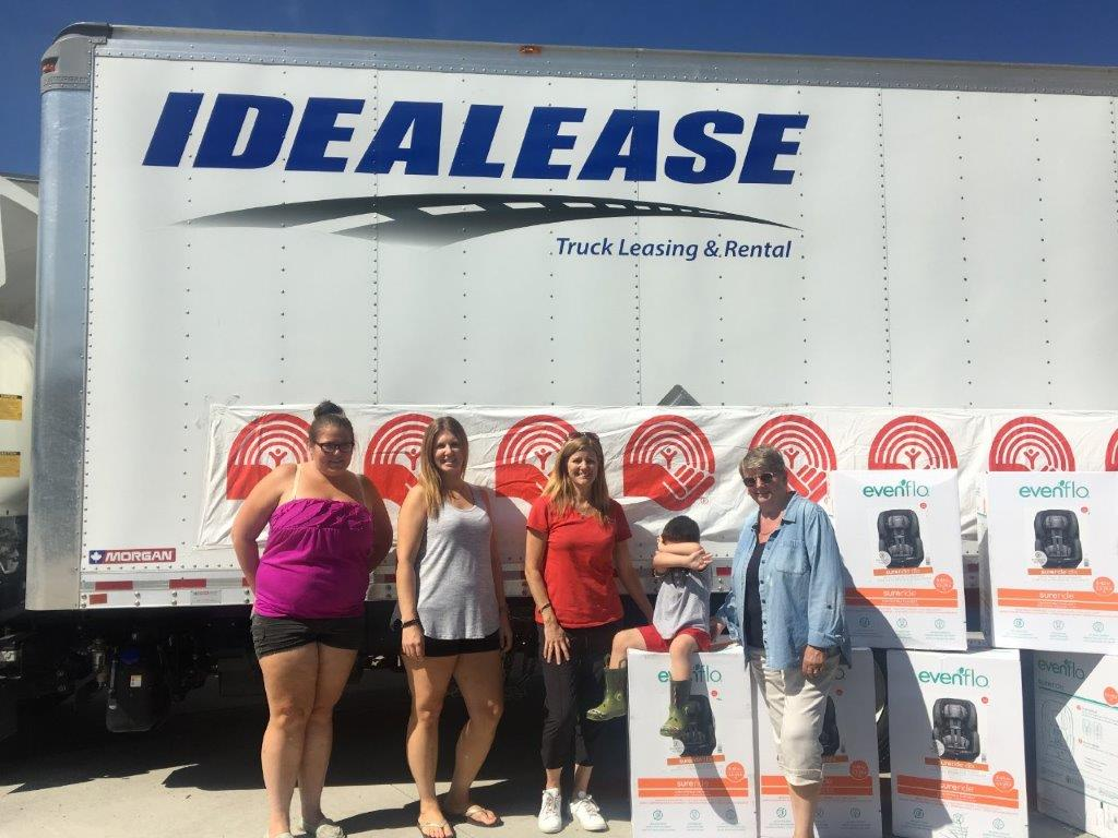 5 people stand with several carseat boxes in front of a moving truck with a United Way banner taped to it. One, a child, covers their face with their hands.