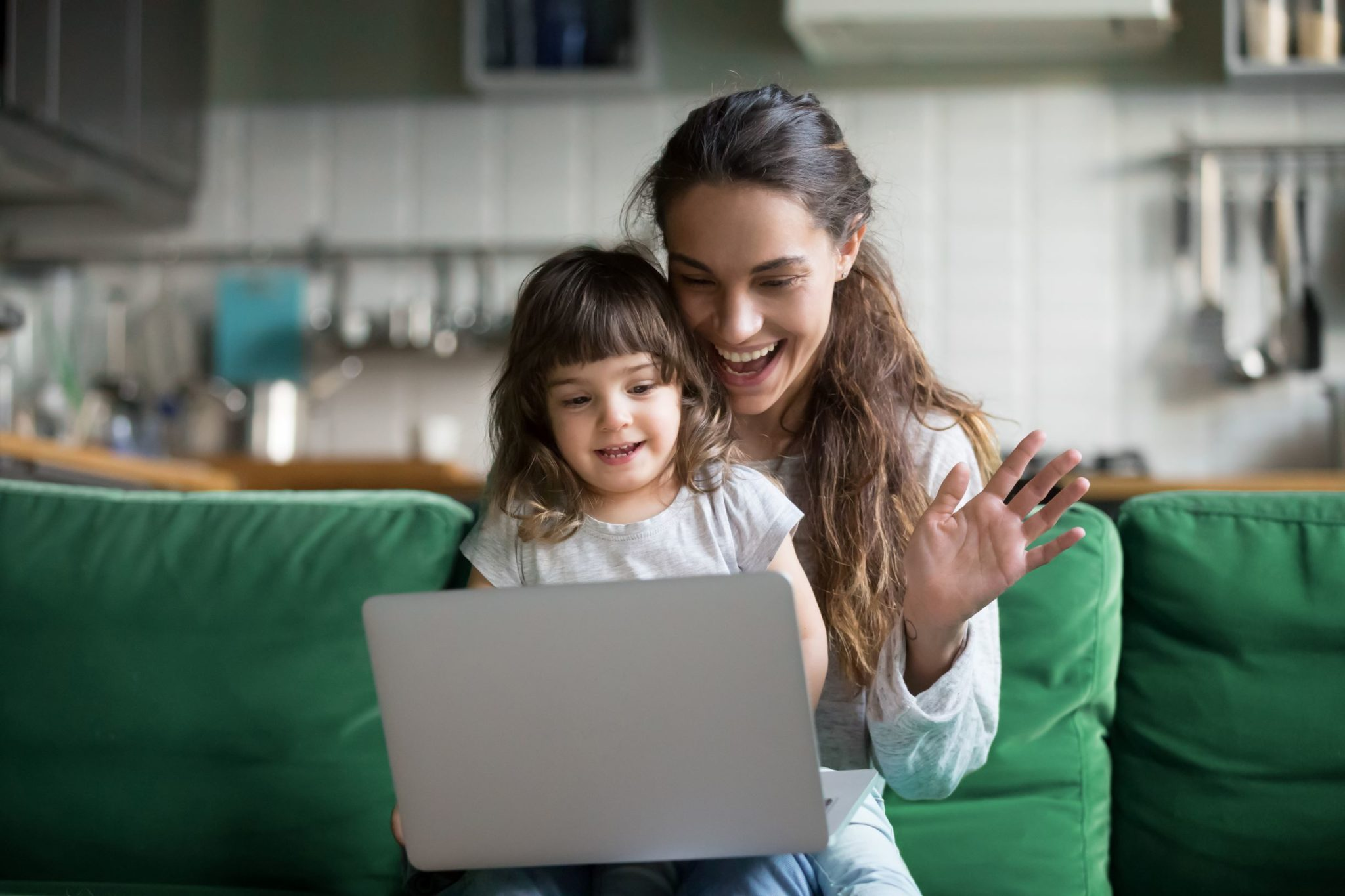 A parent and child happily look at a laptop together.