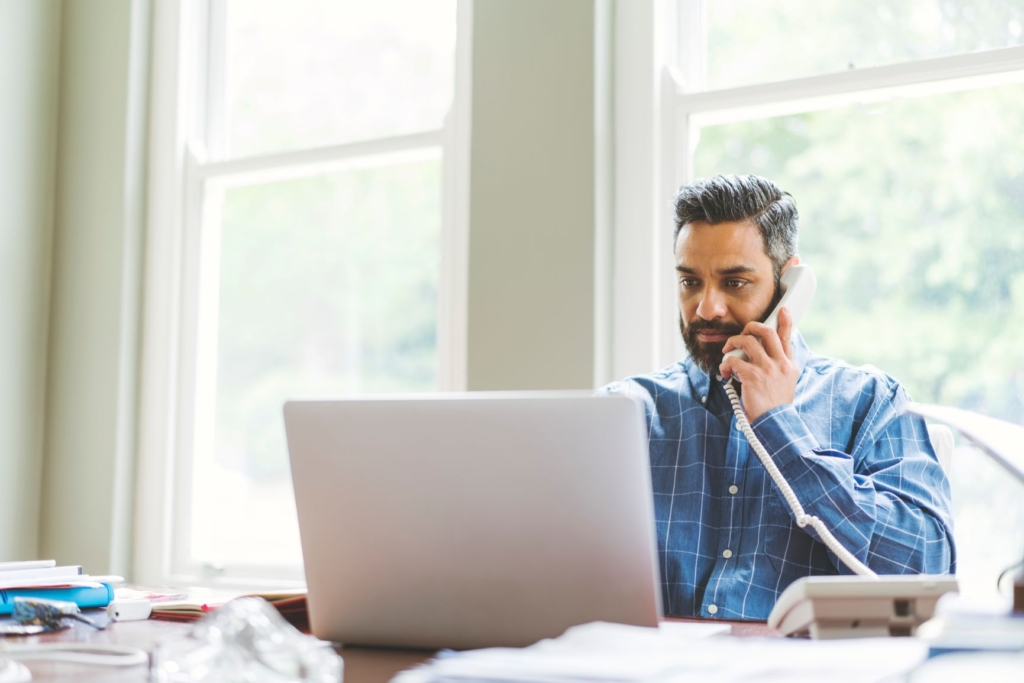 A person listens to a wired desk phone against their ear while looking at a laptop.