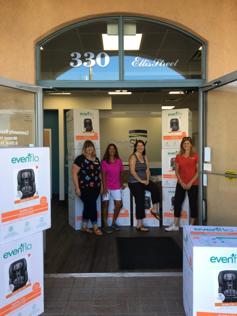 4 people stand inside a doorway, surrounded by several car seat boxes.