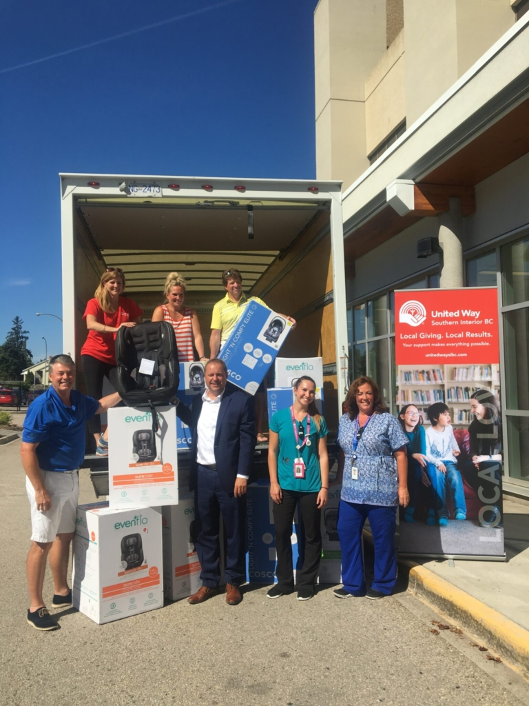 7 people stand in and around the back of a moving truck with several carseat boxes and a United Way banner.
