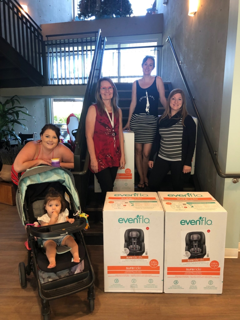 4 adults and a child in a stroller stand in front of a staircase with 2 car seat boxes.