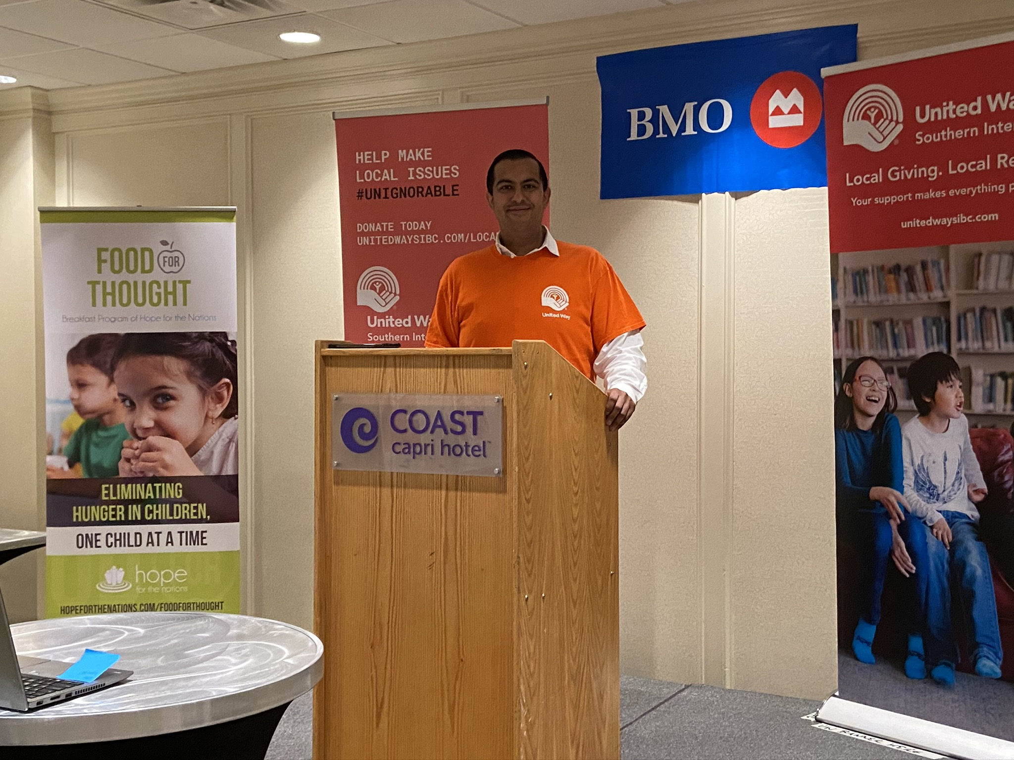 Kahir Lalji stands at a Coast Capri Hotel podium in front of banners for Food for Thought, Help Make Local Issues Unignorable, BMO, and United Way SIBC.