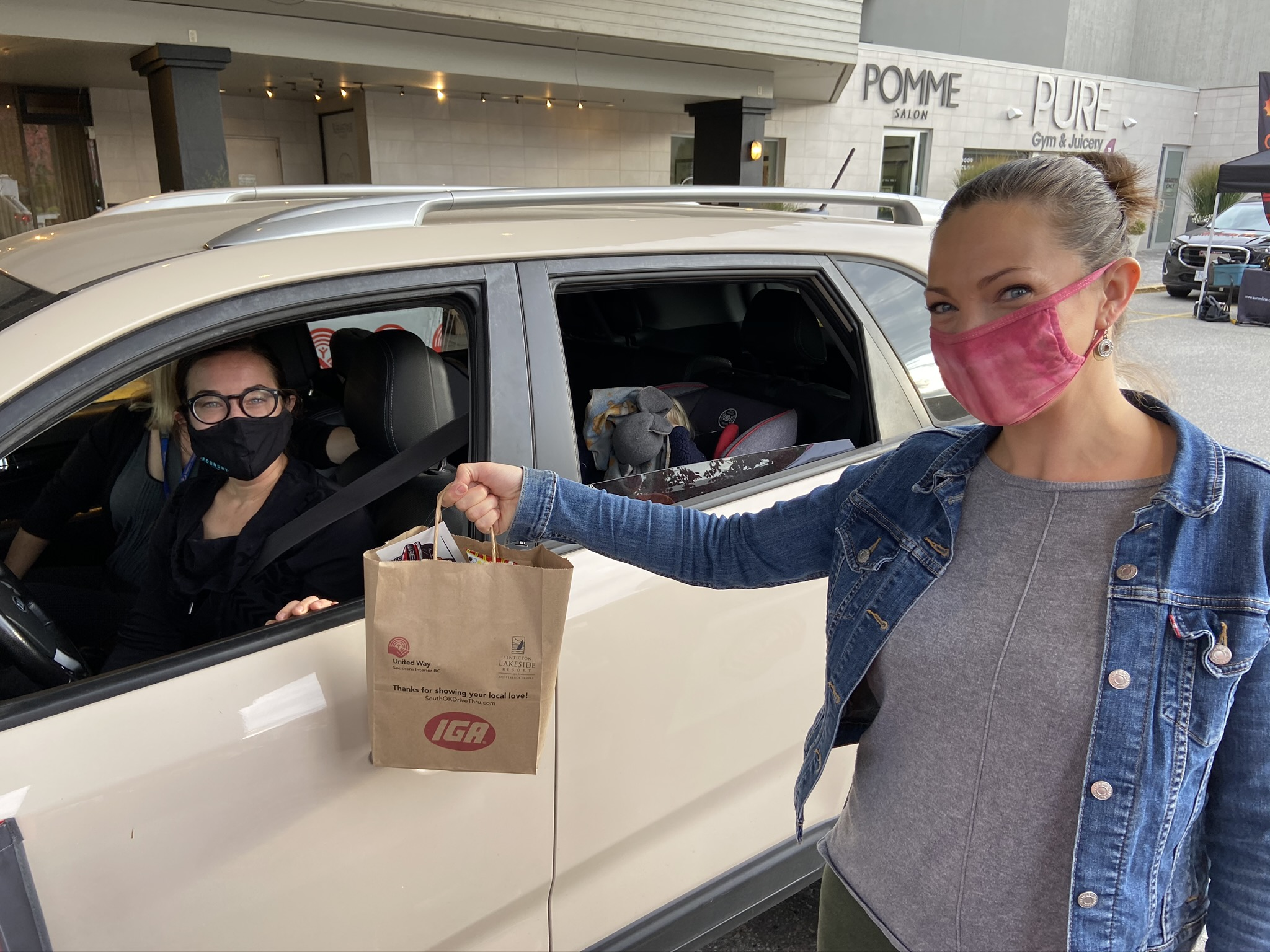 A volunteer hands a paper bag to someone sitting in a car.