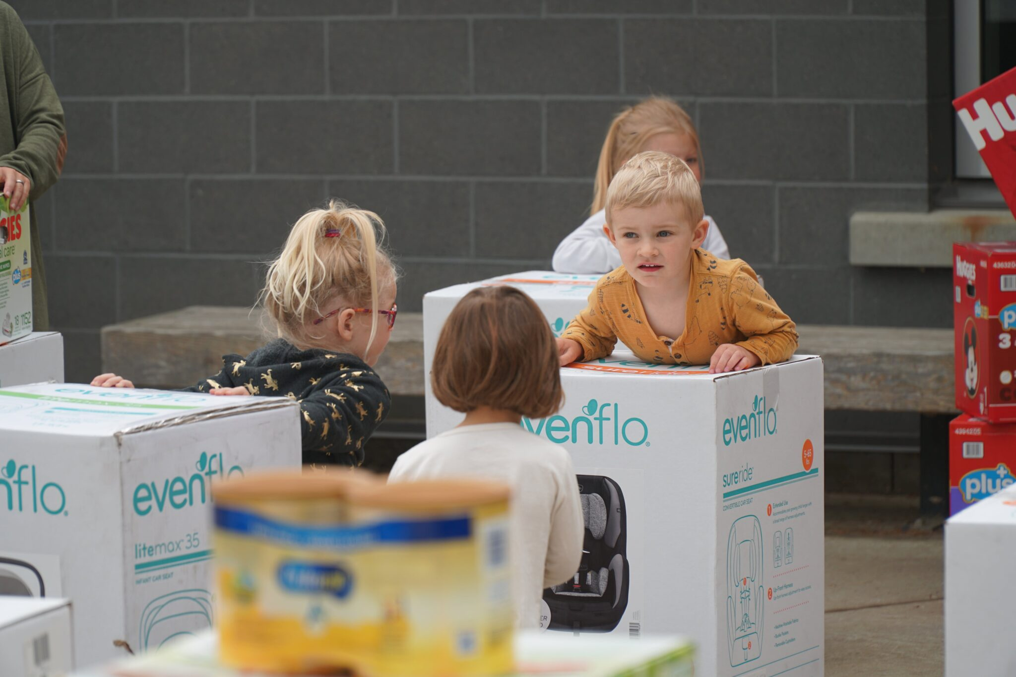 Several children sit or stand around car seat boxes. Other baby products are visible in the background and out of focus in the foreground.