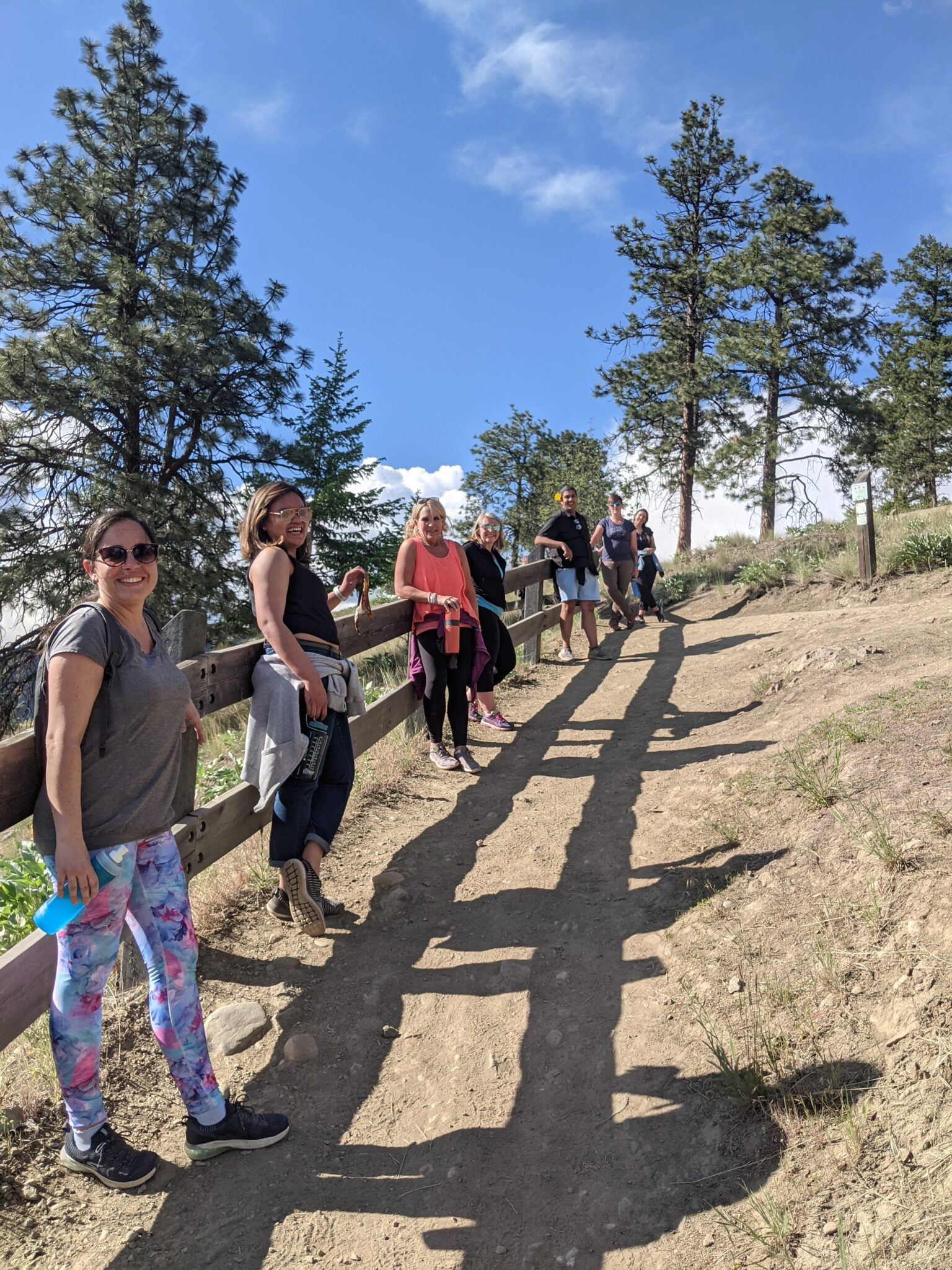 7 people lean on a fence along a dirt trail.