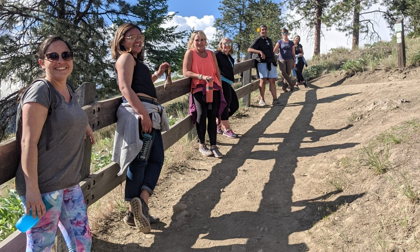 7 people face the camera while leaning on a fence along an uphill outdoor trail.