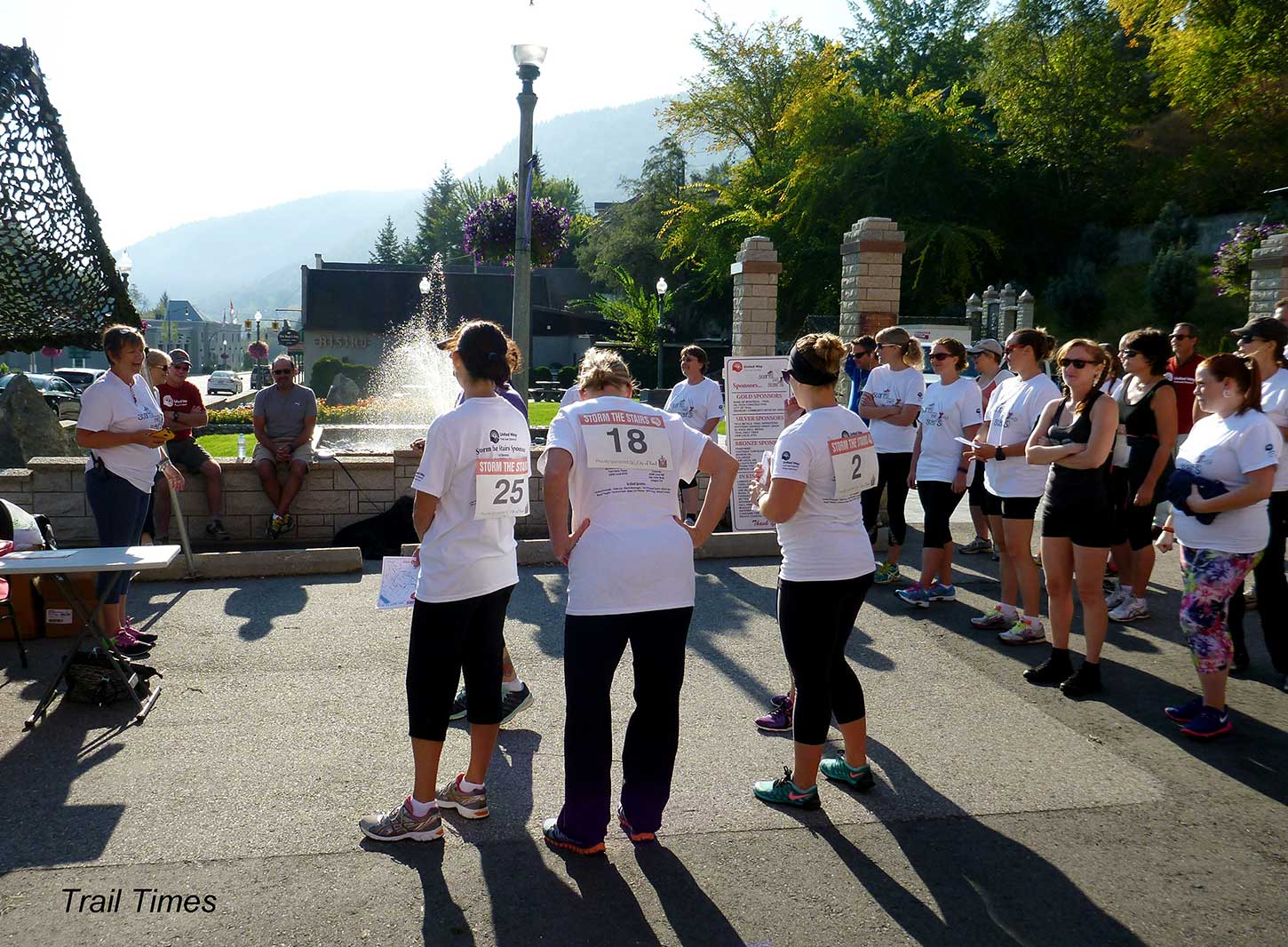 3 people with race numbers on their backs stand next to a fountain.